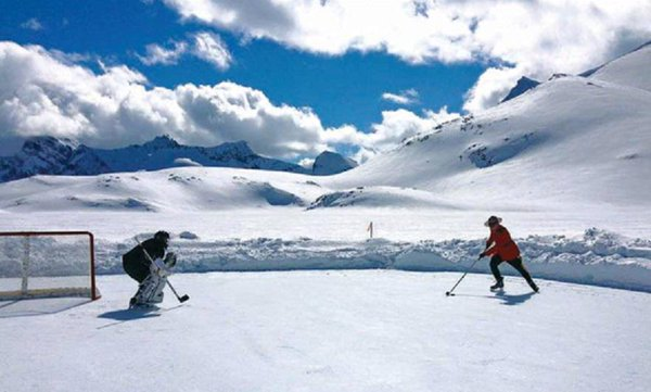 Mountie Shaun Begg playing a game of shinny on a rink built on a glacier near Invermere