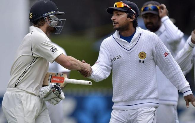 New Zealand's Kane Williamson (L) shakes hands with Sri Lanka's Kumar Sangakkara as they walk off the ground for lunch on day four of the second international Test cricket match between New Zealand and Sri Lanka at the Basin Reserve in Wellington on January 6, 2015.   AFP PHOTO / MARTY MELVILLE        (Photo credit should read Marty Melville/AFP/Getty Images)