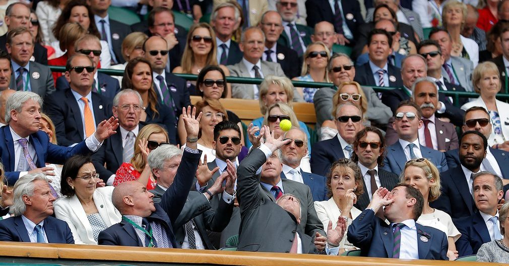 Prince Andrew tries to catch a ball deflected into the Royal Box during the Roger Federer v Milos Raonic semi