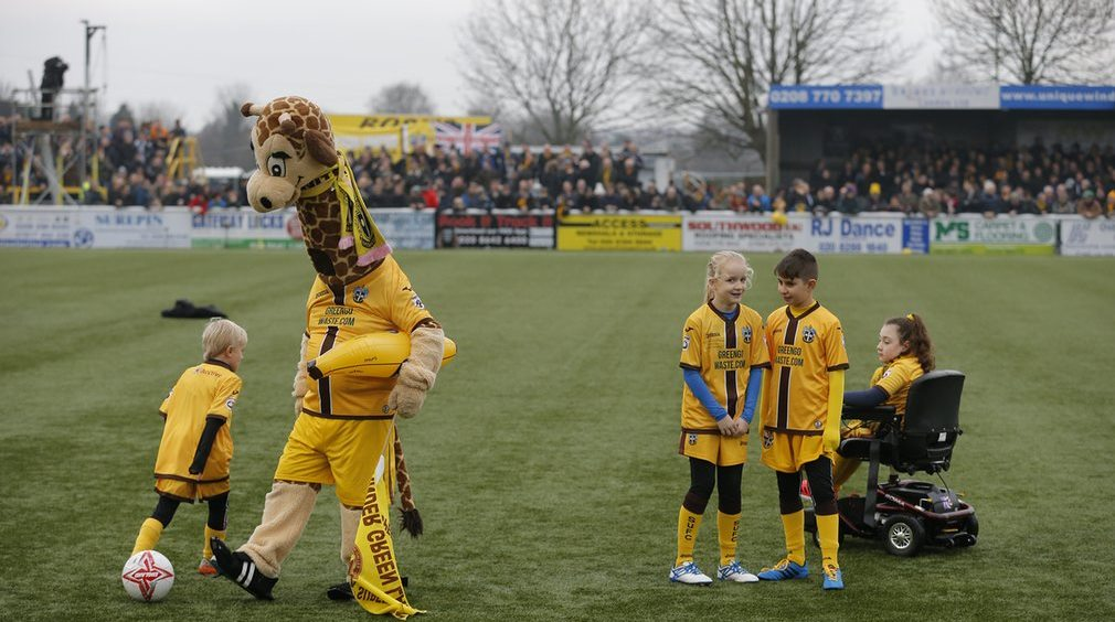 The Sutton mascot, Jenny the Giraffe, entertains the mascots and supporters. AFC Wimbledon