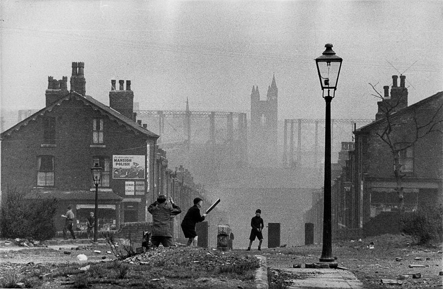 Children playing cricket in the street with a broken paving stone as the wicket Complete with gas lamp and smog Leeds 1954