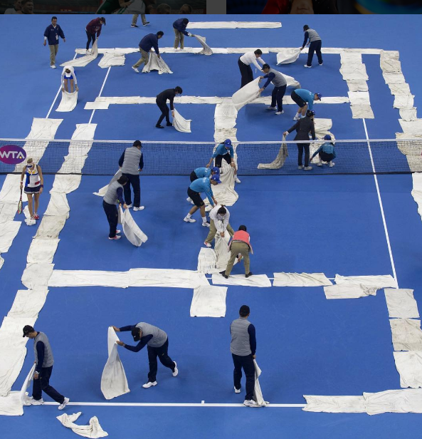 Officials and players help to dry the court before the women's doubles final at the China Open