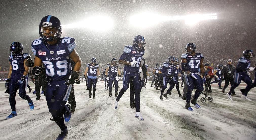 Argonauts run on to a snowy field before the start of the Grey Cup game against the Calgary Stampeders