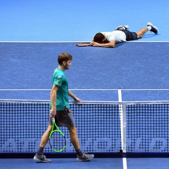David Goffin waits at the net as Grigor Dimitrov reacts to his victory at the ATP World Tour Finals.